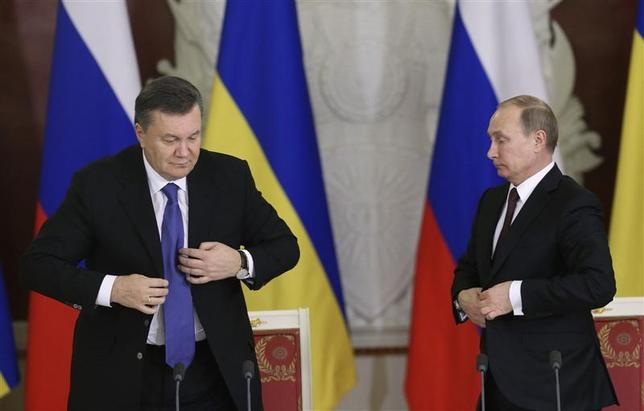 Russia's President Vladimir Putin (R) and his Ukrainian counterpart Viktor Yanukovich button their jackets during a signing ceremony after a meeting of the Russian-Ukrainian Interstate Commission at the Kremlin in Moscow, December 17, 2013. REUTERS/Sergei Karpukhin