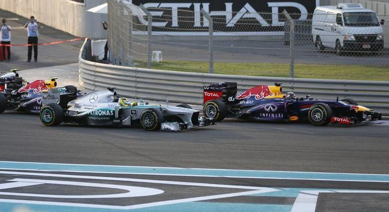 Red Bull Formula One driver Sebastian Vettel of Germany (R) drives ahead of Mercedes Formula One driver Nico Rosberg of Germany and Red Bull Formula One driver Mark Webber of Australia (L) during the Abu Dhabi F1 Grand Prix at the Yas Marina circuit on Yas Island, November 3, 2013 File Photo. REUTERS/Steve Crisp