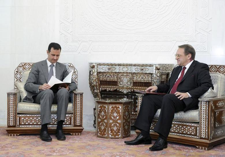 Syria's President Bashar al-Assad (L) reads a message from former Russian President Dmitry Medvedev, during his meeting with Russian Deputy Foreign Minister Mikhail Bogdanov (R) in Damascus August 29 ,2011, in this handout photograph released by Syria's national news agency SANA. REUTERS/Sana/Handout