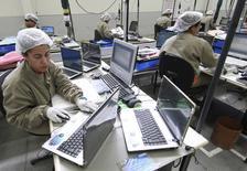 Funcionários trabalham na linha de montagem da Positivo, a maior fabricante brasileira de computadores, em Curitiba. O desemprego brasileiro recuou mais do que o esperado em novembro, voltando à mínima histórica de 4,6 por cento, ao mesmo tempo em que o rendimento voltou a crescer. 25/09/2009 REUTERS/Cesar Ferrari