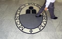 Um homem passa por um logotipo do banco Monte Dei Paschi Di Siena em Roma. As ações do problemático banco italiano Monte dei Paschi di Siena subiam nesta quinta-feira, após o banco firmar acordo para encerrar um negócio de derivativo com o Deutsche Bank que causava prejuízos. 24/09/2013 REUTERS/Alessandro Bianchi