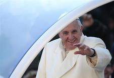 Pope Francis waves as he arrives to lead his Wednesday general audience in Saint Peter's square at the Vatican December 18, 2013. REUTERS/Tony Gentile