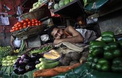 """Fotografía de archivo de un vendedor descanzando a la espera de clientes en una verdulería en Mumbai, India, sep 18 2012. Elecciones en las """"cinco frágiles"""" economías emergentes el próximo año, junto con los espinosos temas de Siria e Irán, complicarán la vida de los inversores a medida que intentan sortear los riesgos políticos en mercados en desarrollo tras un difícil 2013. REUTERS/Vivek Prakash"""