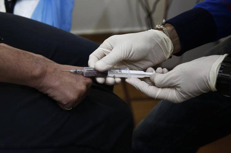 A drug user gives blood sample for a HIV test inside a clinic in Athens November 25, 2013. REUTERS/Yorgos Karahalis
