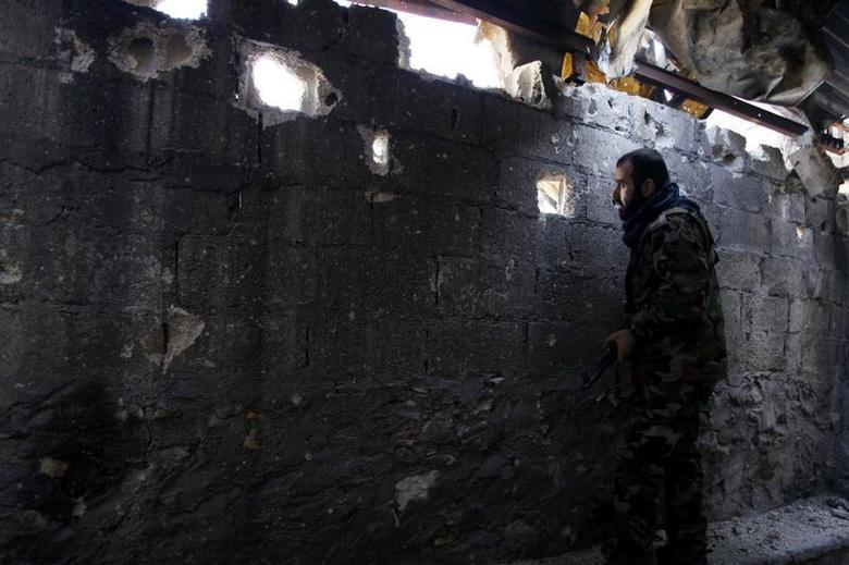 A Free Syrian Army fighter looks through a hole in a wall in Old Aleppo, December 15, 2013. REUTERS/Molhem Barakat