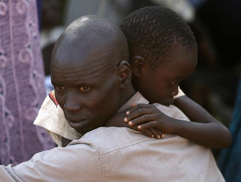 An internally displaced man holds his son inside a United Nations Missions in Sudan (UNMIS) compound in Juba December 19, 2013. REUTERS/Goran Tomasevic