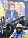 Участник протестов на Площади Независимости на фоне эксрана, транслирующего выступления президенат Украины Виктора Януковича, в Киеве 19 декабря 2013 года. Украина получит меньше денег от Международного валютного фонда в будущем, по сравнению с $15 миллиардами, выделенными для нее в 2010 году, заявил в четверг совет МВФ. REUTERS/Stringer