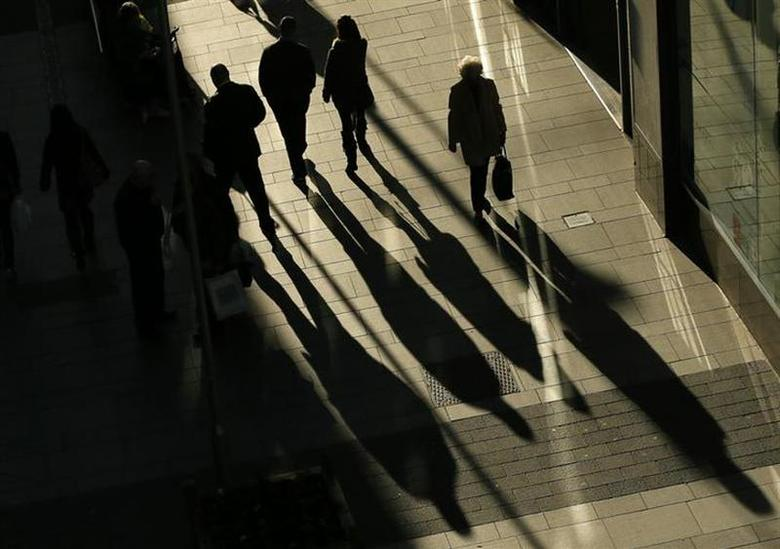 Shoppers cast shadows as they walk along a pedestrianized shopping street in Altrincham, northern England November 19, 2013. REUTERS/Phil Noble