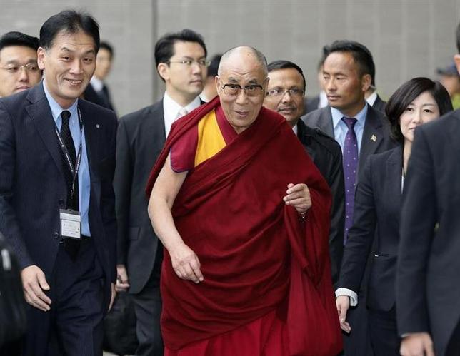 Tibetan spiritual leader, the Dalai Lama (C) arrives at Narita international airport in Narita, east of Tokyo, in this photo taken by Kyodo November 15, 2013. REUTERS/Kyodo