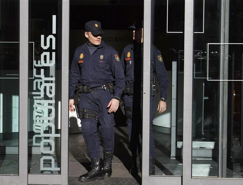 Police officers leave the ruling People's Party (PP) headquarters in Madrid, after police searched the headquarters for 14 hours as part of a corruption investigation that earlier this year threatened to destabilize the government of Prime Minister Mariano Rajoy, December 20, 2013. REUTERS/Paul Hanna