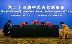 An usher and a hostess prepare a table for a signing ceremony after a meeting of the 24th China-U.S. Joint Commission on Commerce and Trade at the Diaoyutai State Guesthouse in Beijing, December 20, 2013. REUTERS/Alexander F. Yuan/Pool