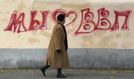 Женщина проходит мимо граффити, посвященного президенту Владимиру Путину, в Москве 7 октября 2012 года. Оптимизм населения по поводу замедления инфляции в России к концу года заметно угас, а уровень его доверия к ЦБР, которому в среднесрочной перспективе предстоит опустить инфляцию до 4 процентов, снизился, следует из исследования инфляционных ожиданий, опубликованного на сайте регулятора. REUTERS/Sergei Karpukhin