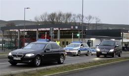Машина, в которой, предположительно, едет Михаил Ходорковский, покидает берлинский аэропорт в сопровождении полиции 20 декабря 2013 года. REUTERS/Fabrizio Bensch