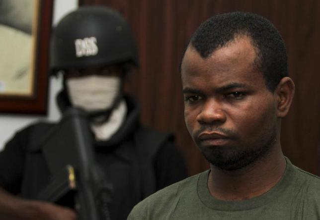 Kabiru Sokoto, a suspect in a Christmas Day bomb attack of St. Theresa Catholic Church in Madalla near Nigeria's capital, is guarded by a security official inside the state security service office in the capital Abuja February 10, 2012. REUTERS/Afolabi Sotunde