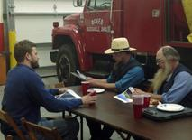 Austin Eudaly (L), an executive with Flatiron Energy Partners, talks with members of the Ohio Amish community at the Deersville, Ohio, Volunteer Fire Department on December 10, 2013.REUTERS/Ernest Scheyder