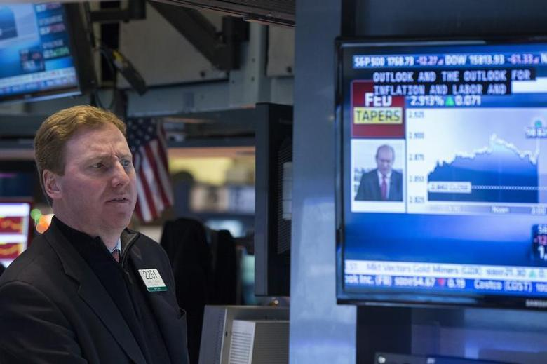 A trader listens to an announcement by the U.S. Federal Reserve on the floor of the New York Stock Exchange in New York December 18, 2013. REUTERS/Lucas Jackson