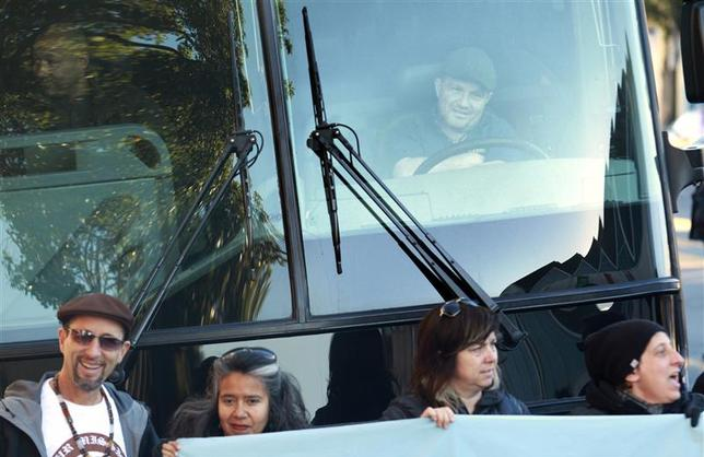 A bus driver, with workers from the technology industry, looks on from his bus as it is blocked during a protest against rising costs of living in San Francisco December 20, 2013. REUTERS/Beck Diefenbach