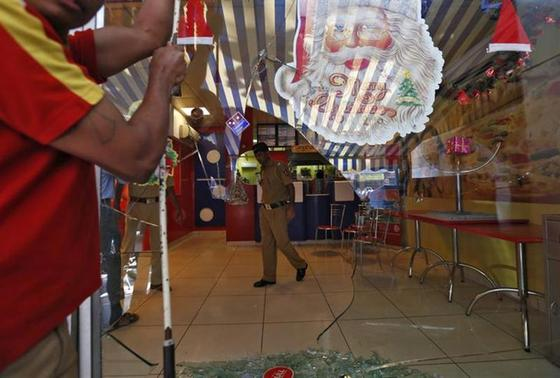 A policeman is seen through a broken glass window of a Domino's Pizza outlet after it was ransacked by activists of the Republican Party of India (RPI) in a Mumbai suburb December 20, 2013. REUTERS/Mansi Thapliyal