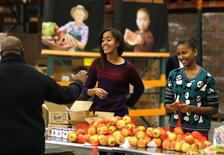 Malia (L) and Sasha (R), daughters of U.S. President Barack Obama and first lady Michelle Obama hand out Thanksgiving food at the Capital Area Food Bank in Washington, November 27, 2013. REUTERS/Larry Downing