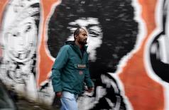 Director Dagmawi Yimer from Ethiopia walks past a mural in downtown Rome November 13, 2013. REUTERS/Tony Gentile