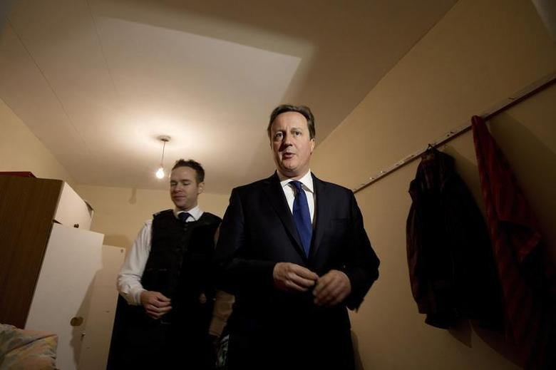 Britain's Prime Minister David Cameron is shown around a house, Immigration officer Paul Wylie, that was raided earlier in the day by Immigration officers, in Southall, west London December 18, 2013. REUTERS/David Bebber/Pool