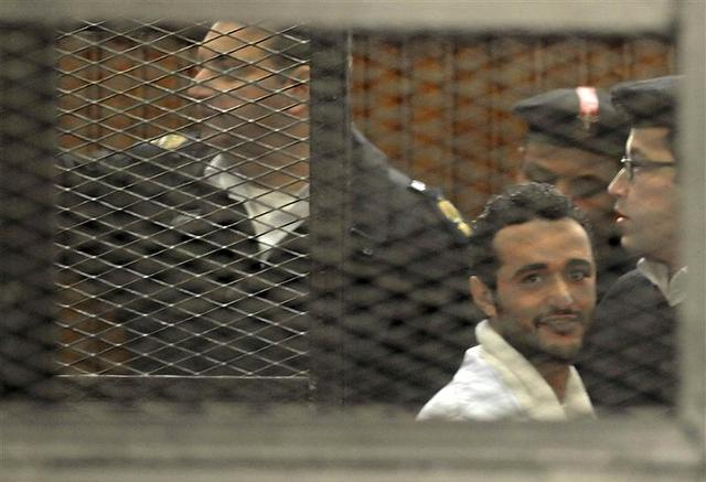 Political activist Ahmed Douma of the 6 April movement looks on behind bars in Cairo, December 22, 2013. REUTERS/Stringer