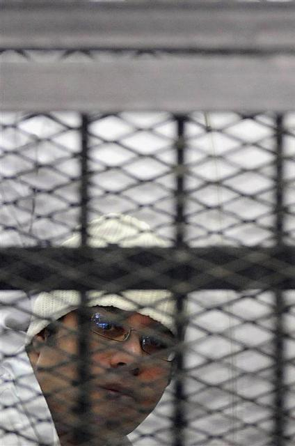 Political activist Ahmed Maher of the 6 April movement looks on behind bars in Cairo, December 22, 2013. REUTERS/Stringer