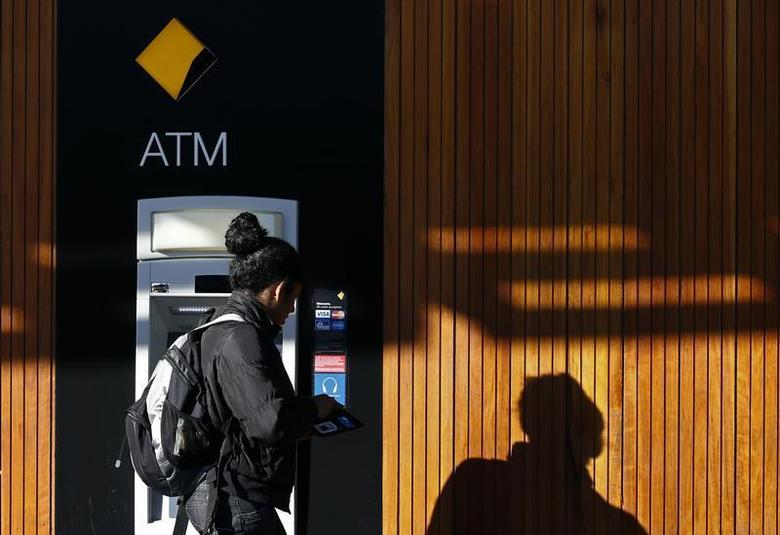 A woman leaves a Commonwealth Bank of Australia ATM in central Sydney August 14, 2013. REUTERS/Daniel Munoz