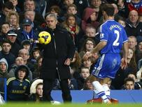 Chelsea manager Jose Mourinho pats the ball to Branislav Ivanovic during their English Premier League soccer match against Crystal Palace at Stamford Bridge, London, December 14, 2013. REUTERS/Andrew Winning