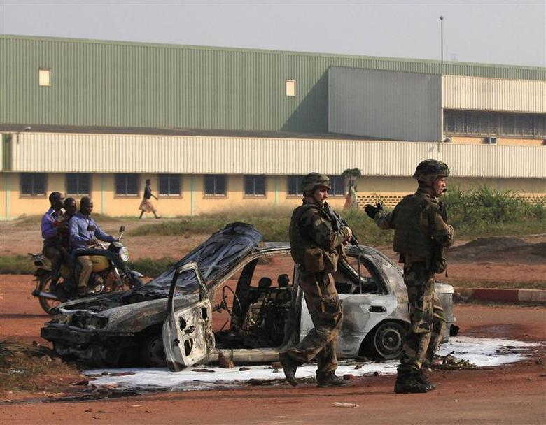French soldiers stand guard near a burnt car from overnight clashes in Bangui December 23, 2013. REUTERS/Andreea Campeanu