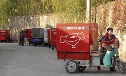 Chen Honglei, 26, um entregador da Jingdong, também conhecida como JD.com, prepara seu tricíclo elétrico antes de deixar a estação de entregas da empresa no distrito de Haidian em Pequim. O JD.com, o segundo maior site de comércio eletrônico da China, deve ultrapassar 100 bilhões de iuanes (16,47 bilhões de dólares) em vendas anuais pela primeira vez em um mercado que tem atraído investimentos de nomes globais do varejo como Amazon e Wal-Mart. 20/11/2013 REUTERS/Paul Carsten