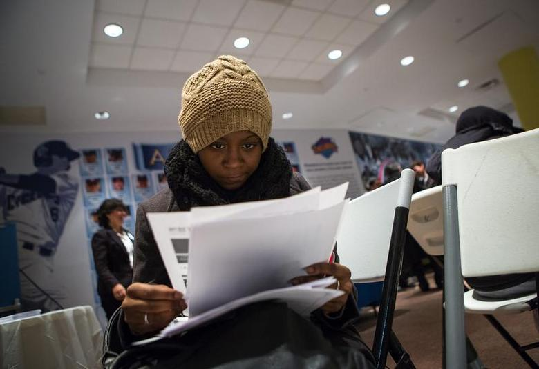 A woman fills out paperwork at a job training and resource fair at Coney Island in New York December 11, 2013. REUTERS/Eric Thayer