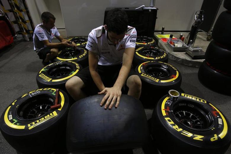McLaren Formula One team members inspect Pirelli tires near the pits ahead of the Singapore F1 Grand Prix September 20, 2012. REUTERS/Edgar Su