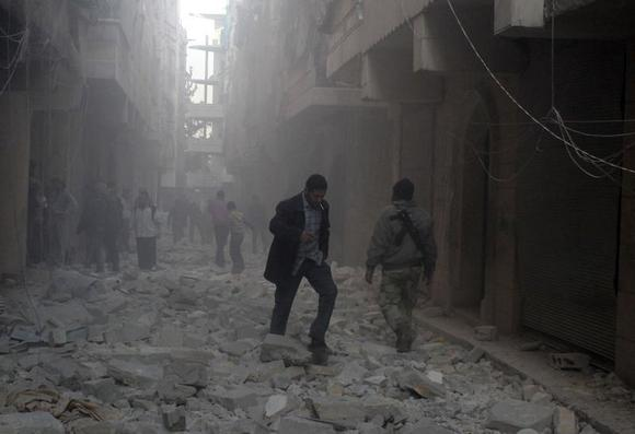 People walk on rubble at a damaged site after what activists said was an air raid by forces loyal to Syrian President Bashar Al-Assad, in Aleppo's al-Saliheen district December 23, 2013. REUTERS/Saad AboBrahim