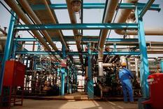 El petróleo cayó el lunes debido a que los operadores tomaron ganancias luego de tres días de avance, aunque el monto negociado fue débil antes del feriado de Navidad. En la foto de archivo, un trabajador en una refinería en Najaf, Irak. Oct 3, 2013. REUTERS/Ahmad Mousa
