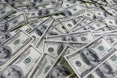 """Долларовые купюры в банке в Сеуле 9 января 2013 года. Российская инвесткомпания O1 Properties, специализирующаяся на коммерческой недвижимости и принадлежащая банкиру Борису Минцу, покупает офисный центр """"Легенда"""" в Москве у девелопера Capital Group, сообщила компания во вторник. REUTERS/Lee Jae-Won"""