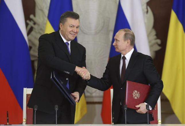 Russia's President Vladimir Putin (R) shakes hands with his Ukrainian counterpart Viktor Yanukovich during a signing ceremony after a meeting of the Russian-Ukrainian Interstate Commission at the Kremlin in Moscow, December 17, 2013. Russia will buy $15 billion worth of Ukrainian securities, Putin said after talks with Yanukovich in the Kremlin on Tuesday. REUTERS/Sergei Karpukhin