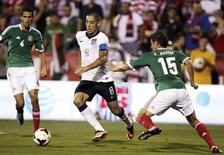 United States' midfielder Clint Dempsey (8) takes the ball past Mexico's Diego Reyes (4) and Hector Moreno (15) during the first half of their 2014 World Cup qualifying soccer match in Columbus, Ohio September 10, 2013. REUTERS/Matt Sullivan