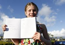 Ten year-old Krystin Lavelle, on vacation with her family from Toronto Canada, holds up an autograph from U.S. President Barack Obama she received during Obama's visit to Marine Corps Base Hawaii in Kaneohe, Hawaii December 24, 2013. REUTERS/Kevin Lamarque