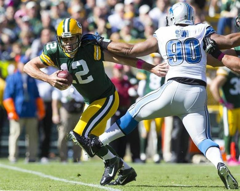 Green Bay Packers quarterback Aaron Rodgers (12) runs with the ball in front of Detroit Lions defensive tackle Ndamukong Suh (90) during the first quarter at Lambeau Field. Jeff Hanisch-USA TODAY Sports