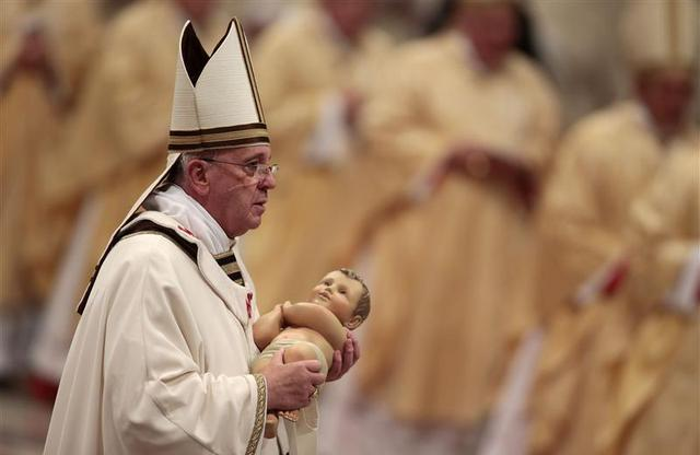 Pope Francis holds the baby Jesus statue at the end of the Christmas night mass in the Saint Peter's Basilica at the Vatican December 24, 2013. REUTERS/Tony Gentile