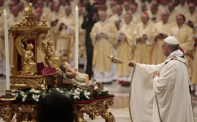 Pope Francis asperges incense on the baby Jesus statue as he leads the Christmas night mass in the Saint Peter's Basilica at the Vatican December 24, 2013. REUTERS/Tony Gentile