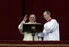 """Pope Francis waves as he delivers his first """"Urbi et Orbi"""" (to the city and world) message from the balcony overlooking St. Peter's Square at the Vatican December 25, 2013. REUTERS/Alessandro Bianchi"""