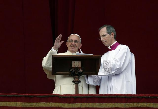 Pope Francis waves as he delivers his first ''Urbi et Orbi'' (to the city and world) message from the balcony overlooking St. Peter's Square at the Vatican December 25, 2013. REUTERS/Alessandro Bianchi
