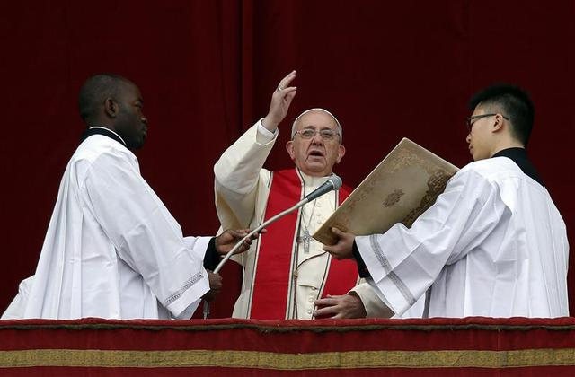 Pope Francis makes a blessing as he delivers his first ''Urbi et Orbi'' (to the city and world) message from the balcony overlooking St. Peter's Square at the Vatican December 25, 2013. REUTERS/Alessandro Bianchi