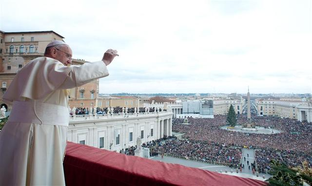 Pope Francis waves as he delivers his first ''Urbi et Orbi'' (to the city and world) message from the balcony overlooking St. Peter's Square at the Vatican December 25, 2013. REUTERS/Osservatore Romano