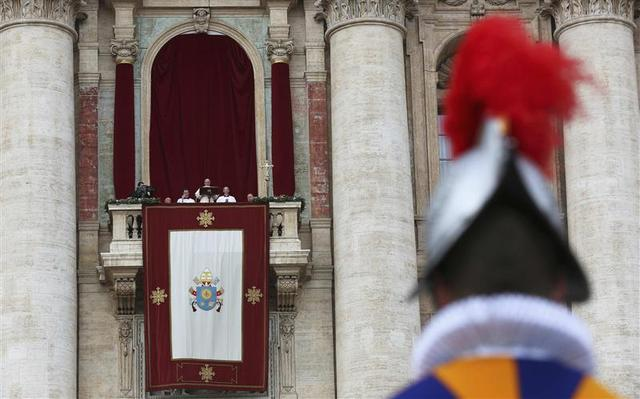 A Swiss Guard stands as Pope Francis delivers his first ''Urbi et Orbi'' (to the city and world) message from the balcony overlooking St. Peter's Square at the Vatican December 25, 2013. REUTERS/Alessandro Bianchi