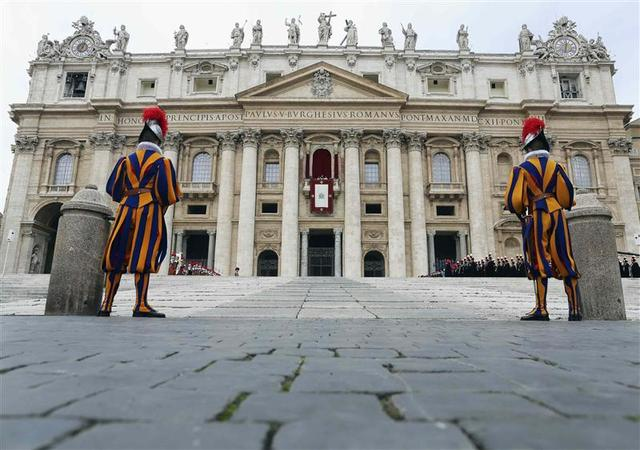 Two Swiss Guards stand as Pope Francis waves as he delivers his first ''Urbi et Orbi'' (to the city and world) message from the balcony overlooking St. Peter's Square at the Vatican December 25, 2013. REUTERS/Alessandro Bianchi