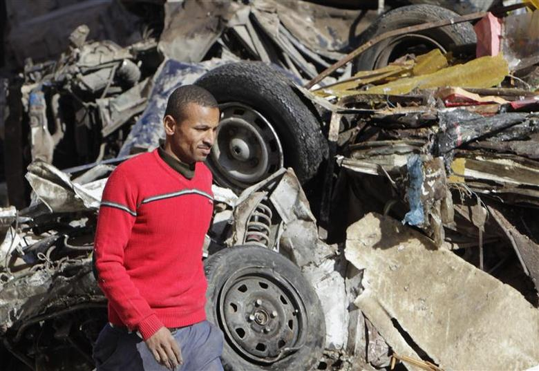 A man walks near a damaged vehicle after an explosion near a security building in Egypt's Nile Delta city of Mansoura in Dakahlyia province, about 120 km (75 miles) northeast of Cairo December 24, 2013. REUTERS/Mohamed Abd El Ghany