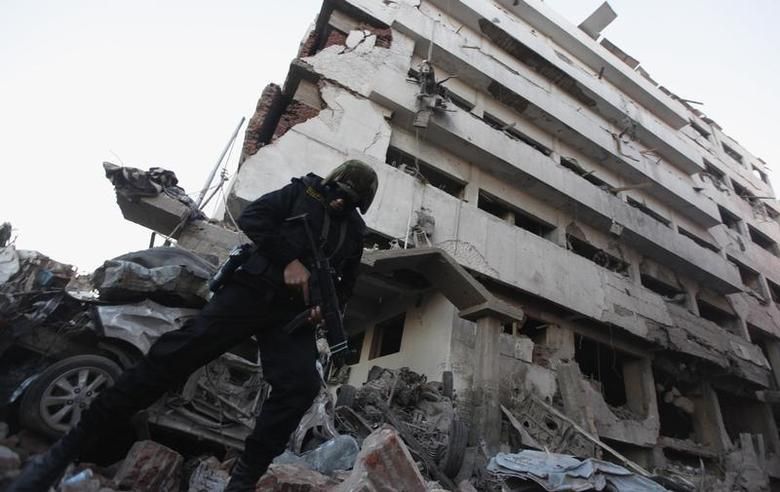 A riot policeman stands outside the building of the Directorate of Security after an explosion in Egypt's Nile Delta town of Dakahlyia, about 120 km (75 miles) northeast of Cairo December 24, 2013. REUTERS/Mohamed Abd El Ghany